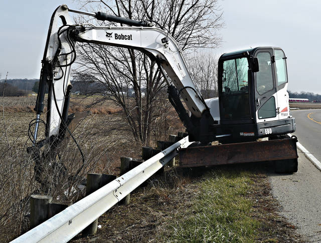 A City of Troy worker trims brush away from the guardrail and ditch along East St.Rt. 41 near the Broadford Bridge on Thursday morning.