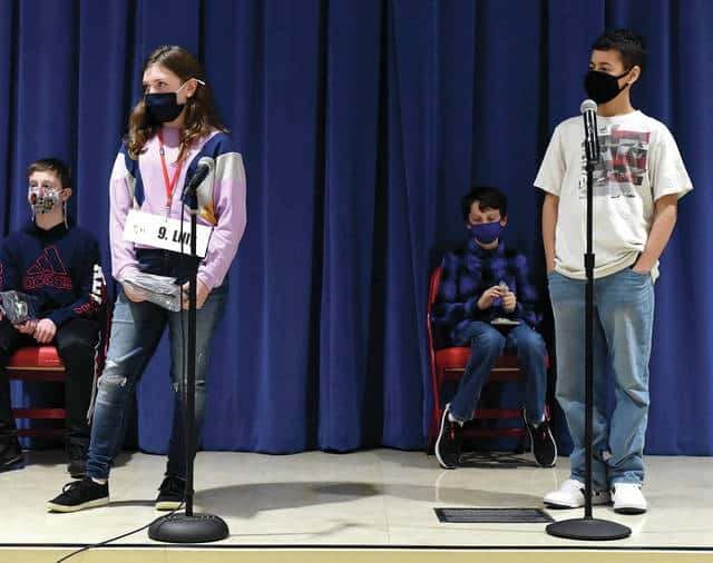Lilly Graham from Piqua Catholic School, standing left, and Elijah Amick from Piqua Junior High School, standing far right, face off as the final two contestants in Thursday's Piqua City-Wide Spelling Bee at Piqua Central Intermediate School. Amick finished the night as the Piqua Spelling Bee champion while Graham was runner-up. The annual event is sponsored by the Piqua Kiwanis Club.