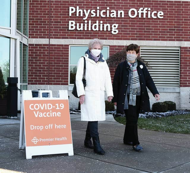 """Dottie Wettstone, left, and Ruth Jenkins, exit Upper Valley Medical Center on Tuesday after receiving their COVID-19 vaccinations at the first Miami County Community Vaccine Clinic by Premier Health. Tuesday was the first """"open"""" clinic for residents who fall into the priority protocols set up by the Ohio Department of Health."""